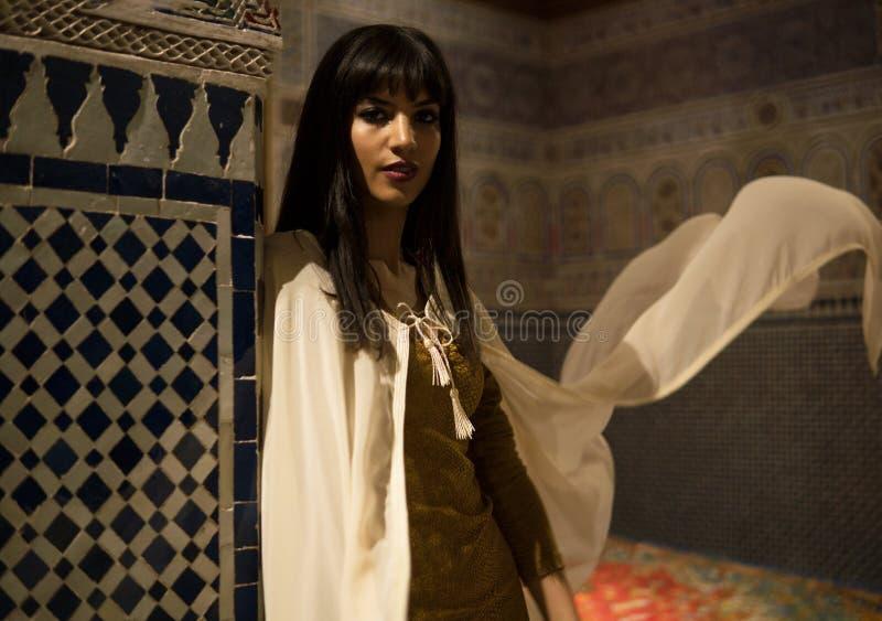 短的金黄礼服和白色披风斗篷的美丽的摩洛哥女孩在美丽如画的达尔Si富有的内部说Riyad 免版税图库摄影
