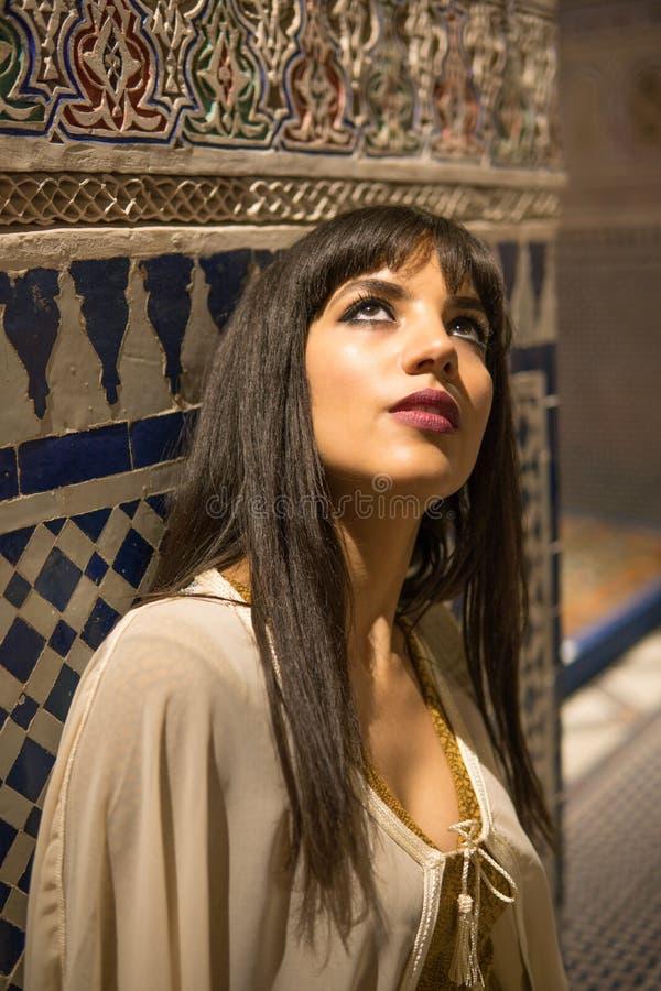 短的金黄礼服和白色披风斗篷的美丽的摩洛哥女孩在美丽如画的达尔Si富有的内部说Riyad 免版税库存照片