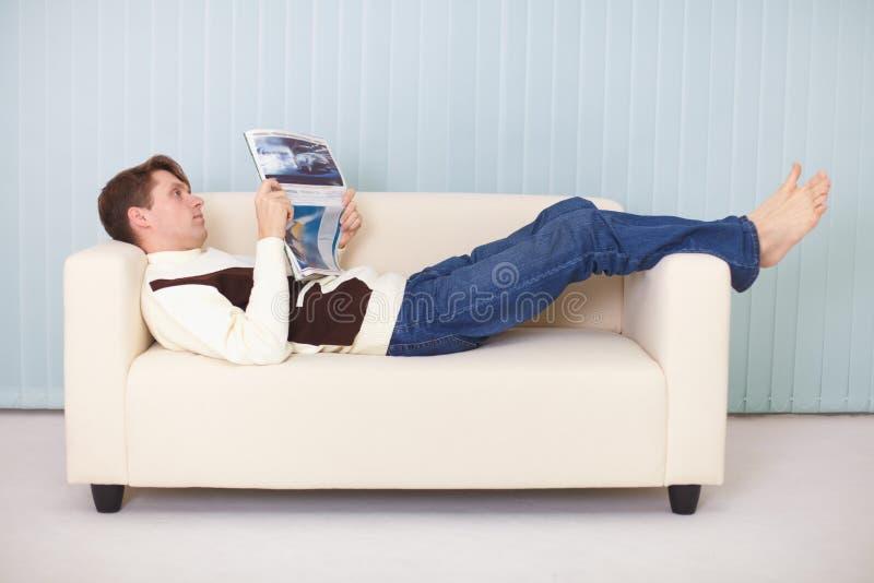 ?an si trova confortevolmente sul sofà con un giornale immagine stock libera da diritti