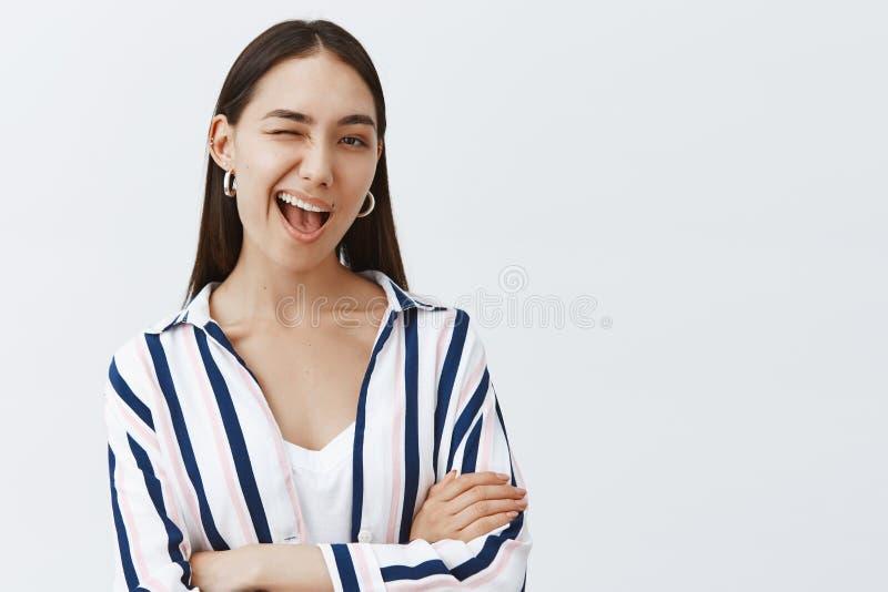 Si vous savez ce que veux dire je Femme mignonne sûre et flirty dans le chemisier rayé, clignant de l'oeil joyeux à la caméra, so photo stock