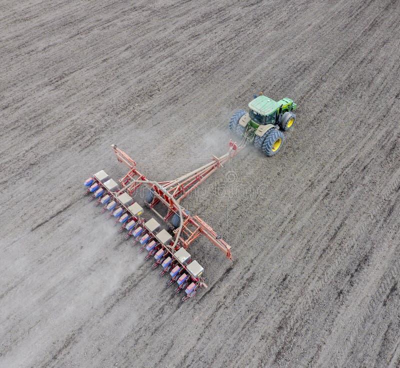 Siać kukurudza Ciągnik z ikrzakiem na polu Używać ziarna obrazy royalty free