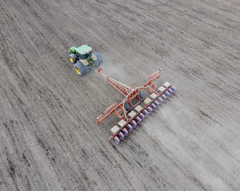 Siać kukurudza Ciągnik z ikrzakiem na polu Używać ziarna zdjęcia stock