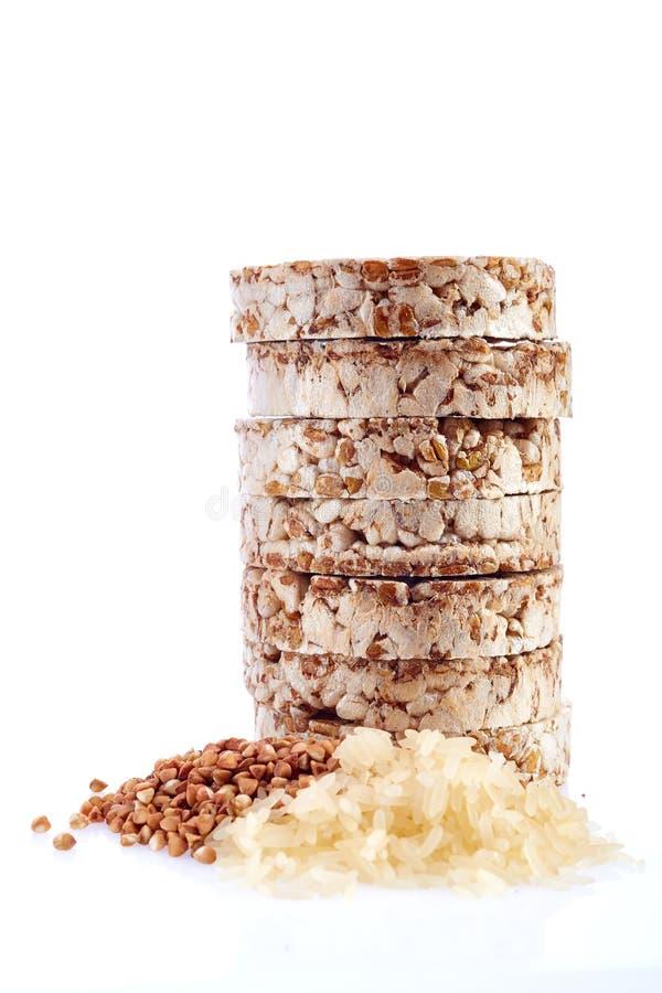 Sia a dieta il mucchio dei dolci di riso con i grani del riso e del grano saraceno isolati su fondo bianco fotografia stock libera da diritti