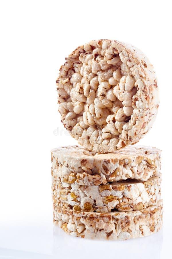 Sia a dieta il mucchio dei dolci di riso con i grani del riso e del grano saraceno isolati su fondo bianco, il verticale, fuoco s immagine stock libera da diritti