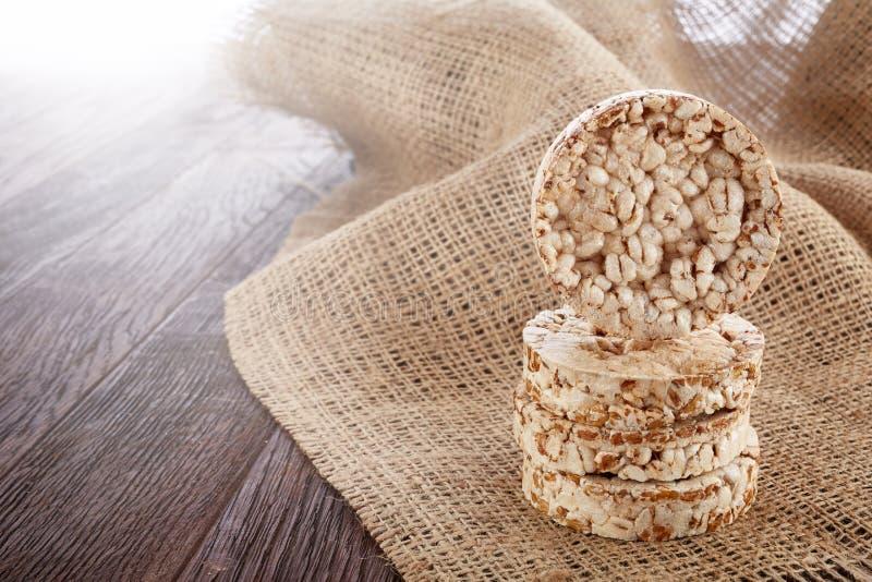 Sia a dieta il mucchio dei dolci di riso sulla tavola di legno coperta di tovagliolo homespun, il fuoco selettivo, lampadina fotografia stock libera da diritti