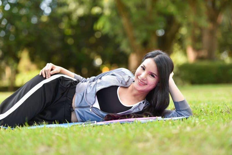 Sia signora di sorriso si rilassano sull'erba fotografia stock