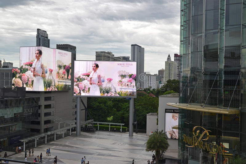 Siam Paragon-winkelcomplex in Bangkok, Thailand met twee het grote reclame buiten scherm stock afbeeldingen