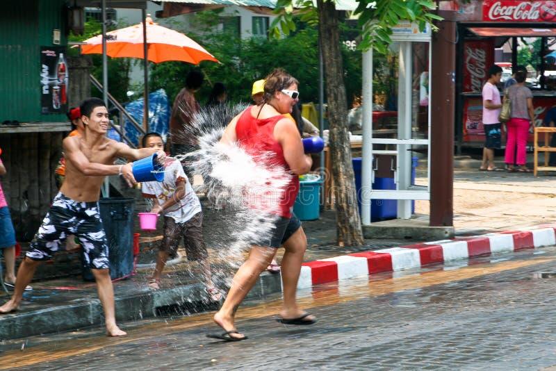 Siamesischer Kerl wirft Wasser am Touristen ein lizenzfreie stockfotografie
