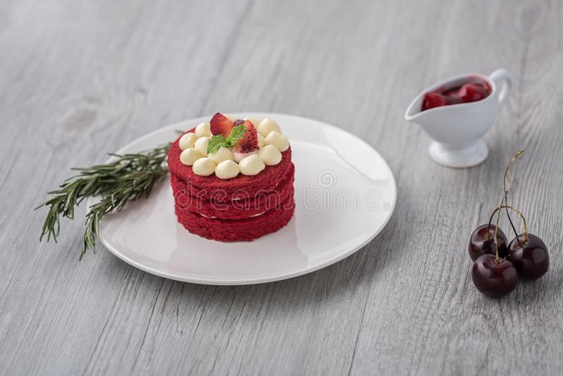 Siamesischer Kuchen Roter Kuchen des Samts Plätzchen verziert mit rotem Kuchen auf Holztisch und Blume moring Erdbeeren Kirsche i lizenzfreies stockfoto