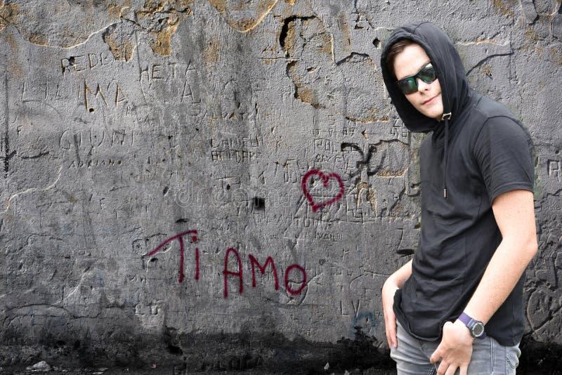 Siamo-grafitti och pojke med den svarta hoodien royaltyfria foton