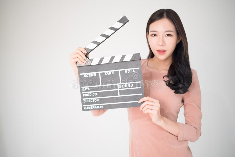 Sian woman holding movie clapper board isolated on white background. Cinematography, communication arts, casting, audition, movie. Production concept. Movie stock photo