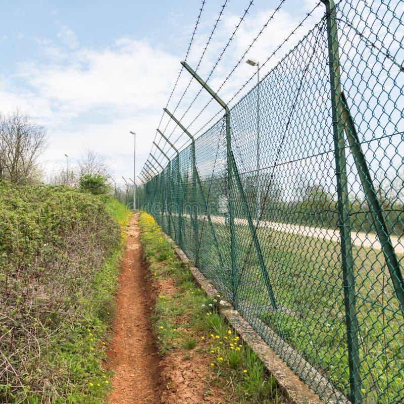 Siatki ogrodzenie nakrywający z drutem kolczastym zdjęcia stock