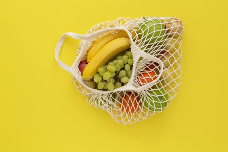 Siatki torba na zakupy z owoc na różowym tle Pojęcie czułość dla środowiska i odrzucenie klingeryt fotografia royalty free