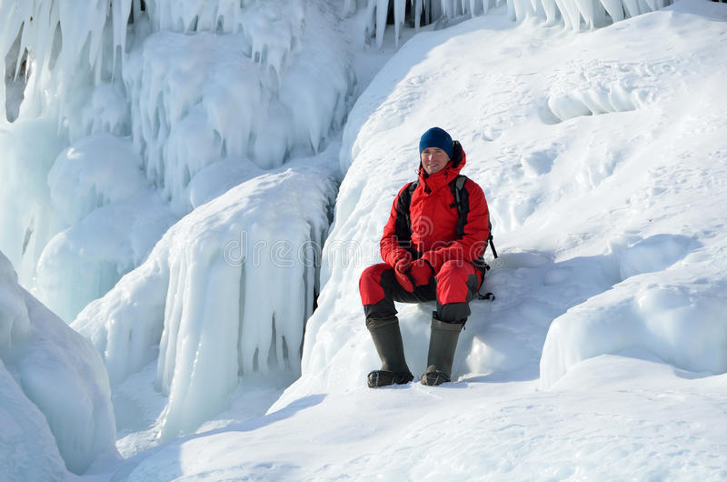 Siberia, lake Baikal, Olkhon island, Cape Khoboy, Russia, February, 22, 2017. Tourist sits on the ice build-up on the shore of Cap stock images