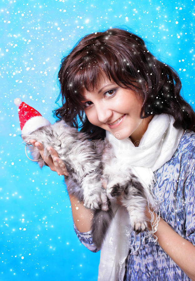 Young woman with kitten in snow. Happy young woman with kitten on in snow stock photography