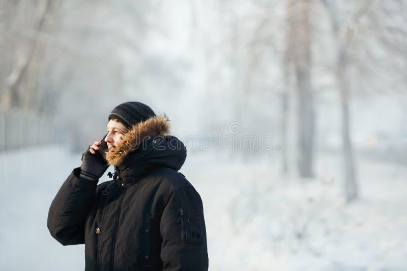 Siberische mens die op de telefoon in openlucht tegen koude dag in de warme winter onderaan jasje met bontkap spreken Sneeuwvorst stock foto's