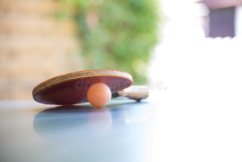 Sibile a raquete e a bola da pá do pong em uma tabela do tênis de mesa foto de stock royalty free