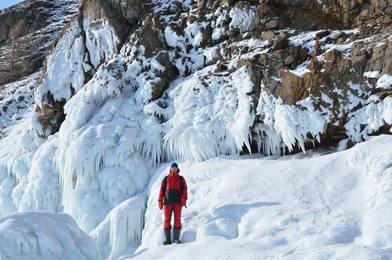 Sibirien Lake Baikal, Olkhon ö, udde Khoboy, Ryssland, Februari, 22, 2017 Turist som går nära isfören mycket på kustnollan royaltyfri foto