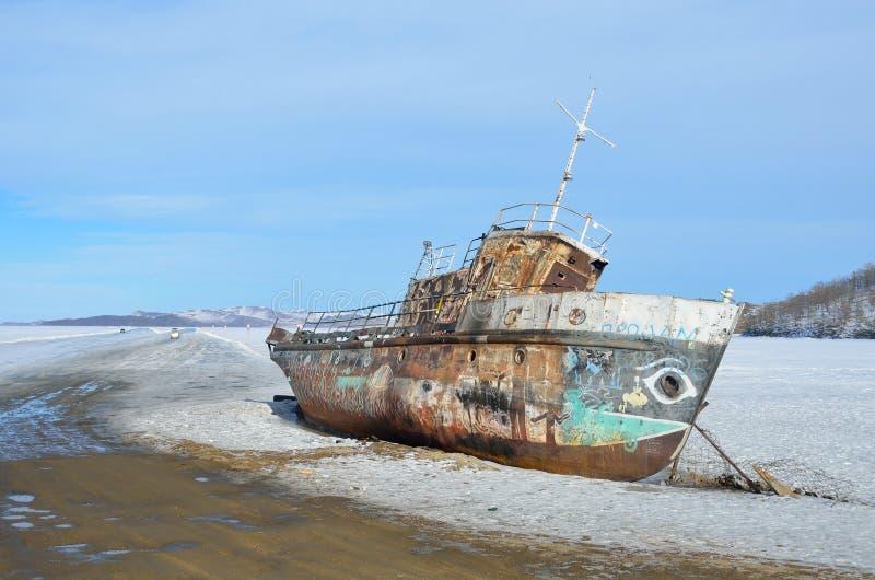 Sibirien Lake Baikal, Olkhon ö, udde Khoboy, Ryssland, mars, 11, 2017 Gammalt rostigt skepp på kanten av den officiella isvägen f arkivfoton