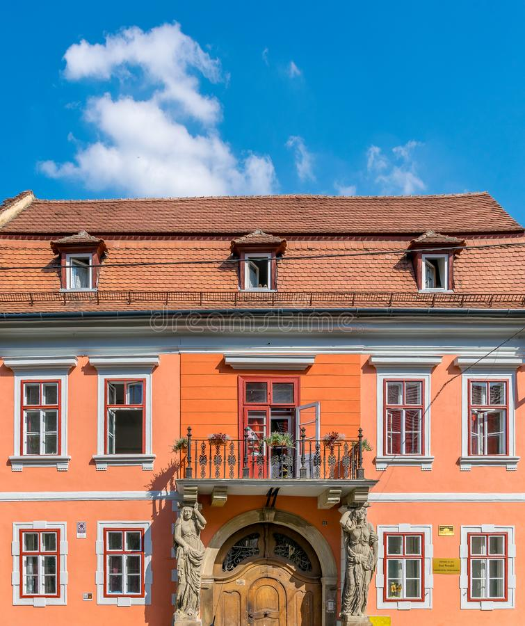 Sibiu, Romania - House with Caryatides - Beautiful house with identical statues and a balcony on a sunny summer day with blue sky royalty free stock image