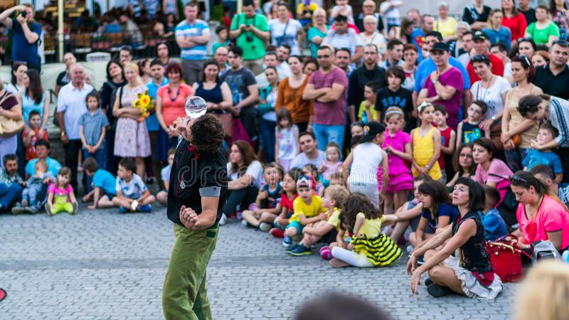 SIBIU, ROMANIA - 17 JUNE 2016: A member of Kinemtatos, Manoamano Circo, Argentina performing a trick in the Little Square during S. Ibiu International Theatre royalty free stock images