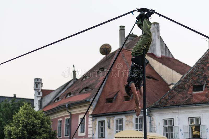SIBIU, ROMANIA - 17 JUNE 2016: A member of Kinemtatos, Manoamano Circo, Argentina performing a trick on the metal bar in the Littl. E Square during Sibiu stock photography