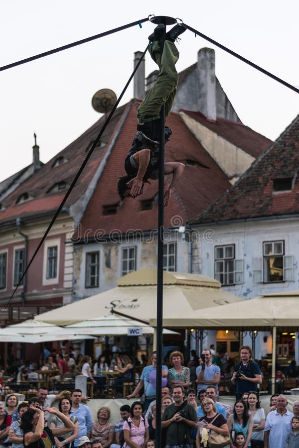 SIBIU, ROMANIA - 17 JUNE 2016: A member of Kinemtatos, Manoamano Circo, Argentina performing a trick on the metal bar in the Littl. E Square during Sibiu royalty free stock image
