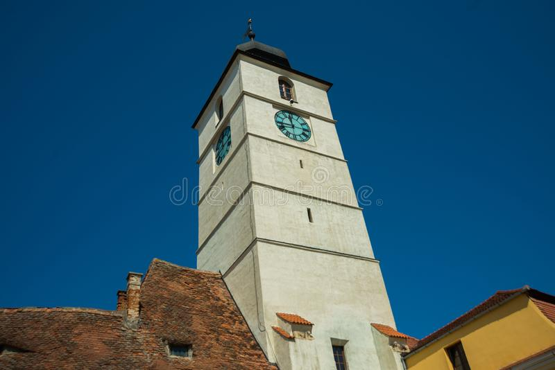 SIBIU, ROMANIA: Sibiu`s council tower in the small swuare on a sunny summer day with a blue sky in Sibiu. SIBIU, ROMANIA : Sibiu`s council tower in the small royalty free stock images