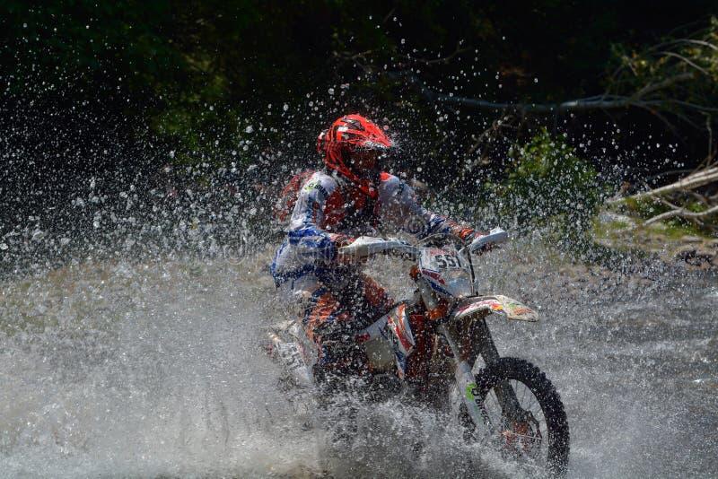 SIBIU, ROUMANIE - 18 JUILLET : Ed Uding concurrençant dans le rassemblement dur de Red Bull ROMANIACS Enduro une moto delorean de photographie stock