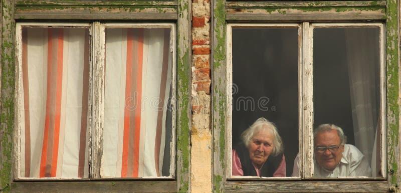 Gamla människor på fönstret i en gammal byggnad royaltyfria foton
