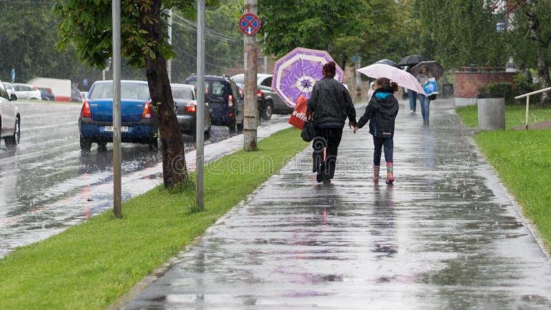 SIBIU, RUMANIA - 25 DE ABRIL DE 2016: Madre y mujer del dother que despierta con un paraguas en una lluvia ventosa en Sibiu, Ruma imagen de archivo libre de regalías