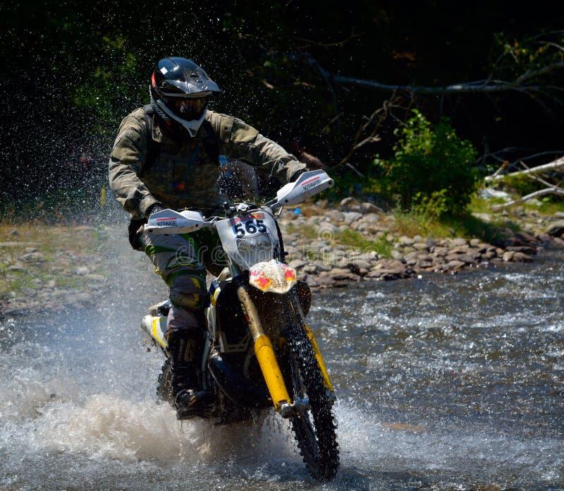 SIBIU RUMUNIA, LIPIEC, - 18: Copetitor w Red Bull ROMANIACS Enduro Ciężkim wiecu z KTM motocyklem Ciężki enduro wiec w t obraz royalty free