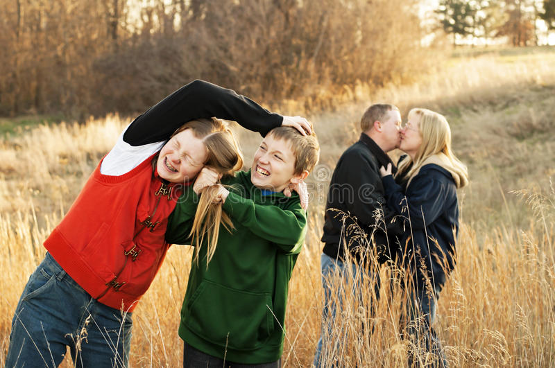 Sibling Rivalry. Realistic family portrayal of a sibling fight in the foreground, while mom and dad kiss in the background royalty free stock images