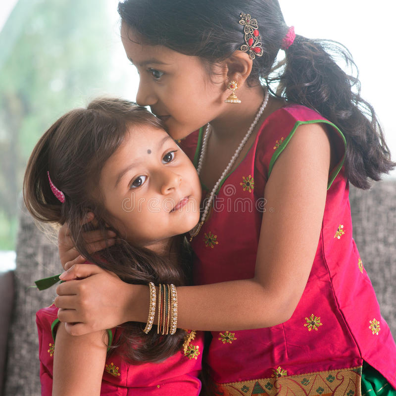 Sibling love. Indian girl kissing her younger sister with love. Asian family at home. Beautiful daughters in traditional India sari stock image