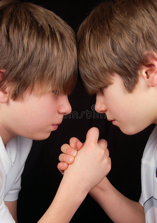 Sibling Rivalry. For these two brothers it's all about who has the upperhand in this arm wrestling match. Each boy thinks it's him royalty free stock images