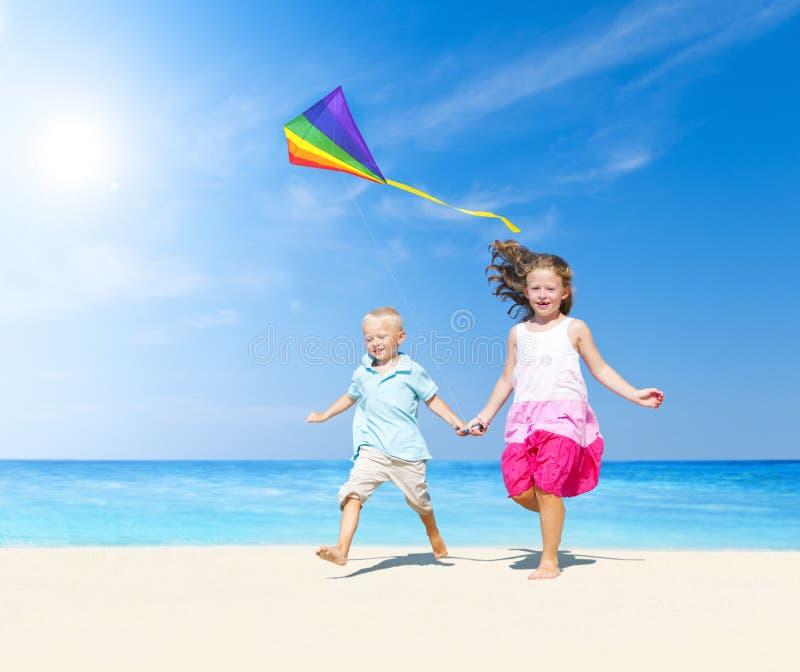 Sibling som tillsammans spelar på stranden royaltyfri fotografi