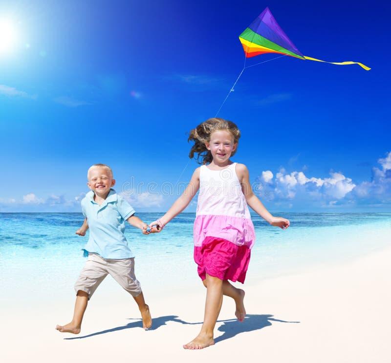 Sibling som tillsammans spelar på stranden arkivbilder