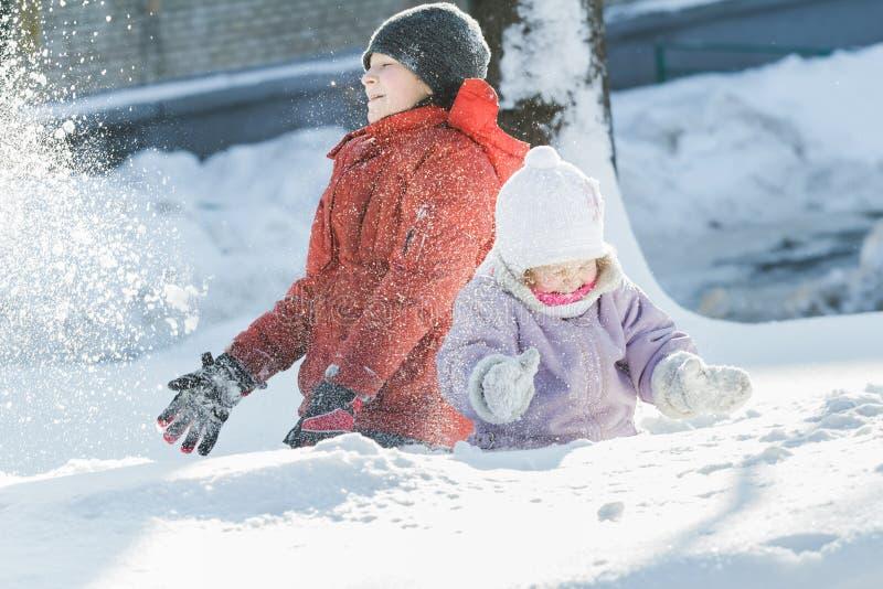 Siblingbarn som gör snöstormen, genom att kasta upp snö under solig dag för frostig vinter utomhus arkivfoton