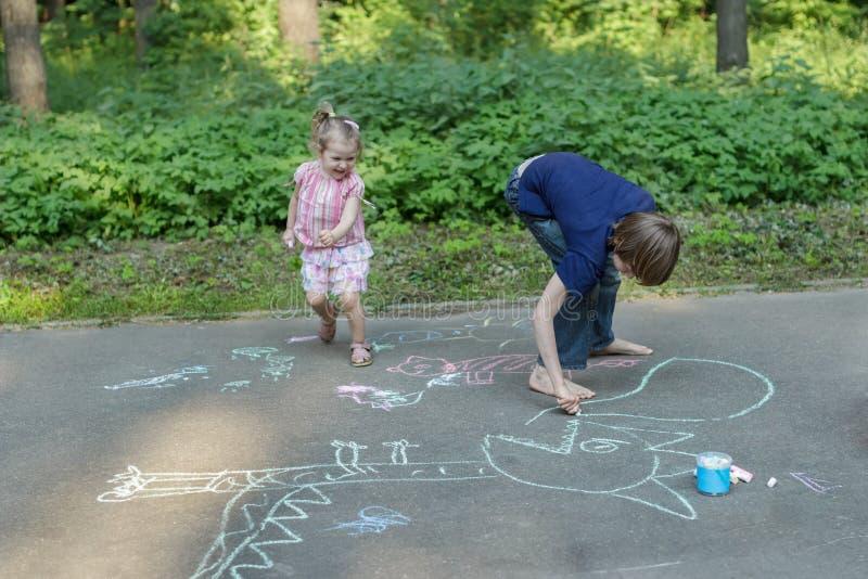 Siblingbarn som har gyckel under trottoaren som chalking på asfaltyttersida fotografering för bildbyråer