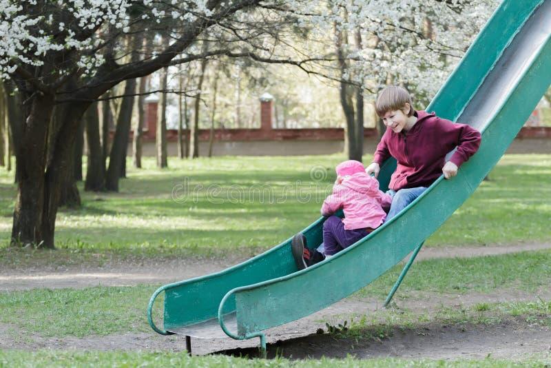 Siblingbarn som ner glider på gammalt, parkerar lekplatsglidbanan på blommande vårfruktträdbakgrund royaltyfri fotografi