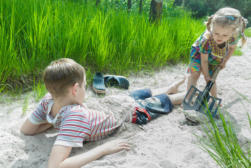 Siblingbarn som spelar på stranddyn och begraver sig i vit sand på tallskogbakgrund royaltyfri fotografi