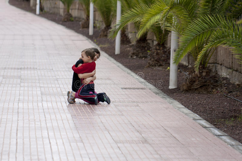 Siblings. Brother and sister embracing on the street stock images