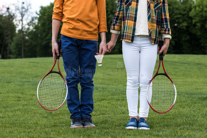 Siblings with badminton racquets holding hands and standing on green grass stock photography