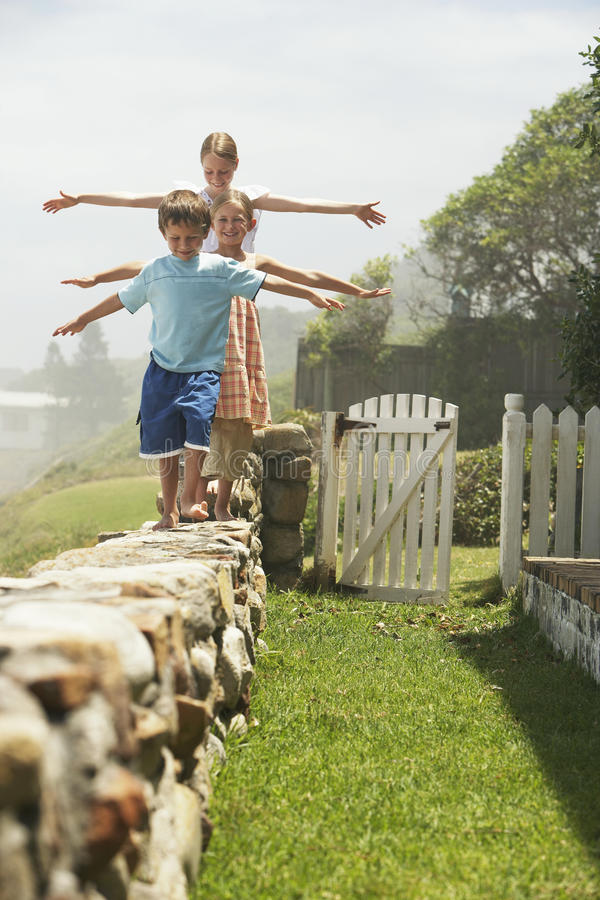 Siblings Balancing While Walking In A Row On Stone Wall stock photography