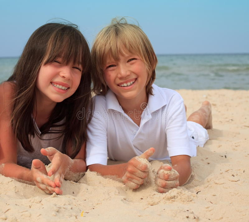 Siblings at the beach. Young sister and brother lay together on a sunny beach royalty free stock photos