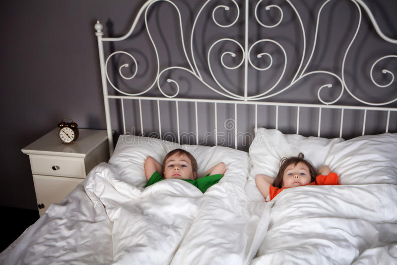 Siblings in bed. Sister and Brother sleeping in their parents bed with an alarm clock set stock photography