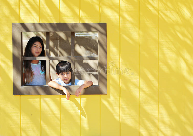 Siblings. Behind little decorative windows royalty free stock photos