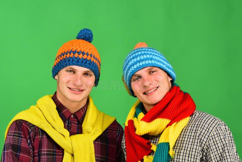 Siblings bevinden zich dicht en glimlachen Kerels in gebreide sjaals stock afbeelding
