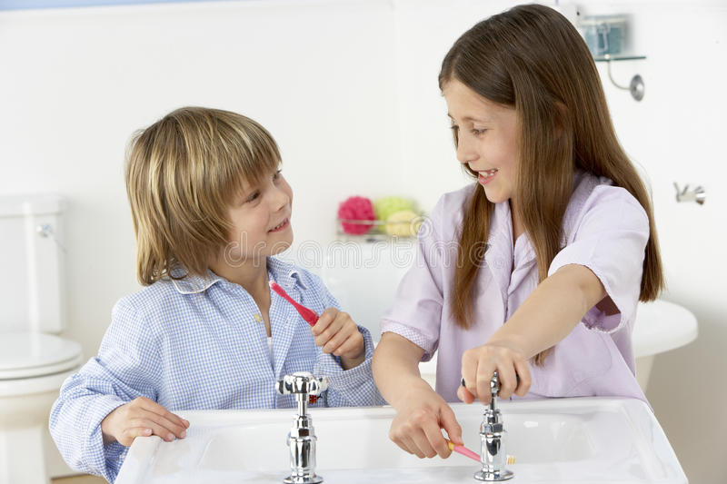 Siblings Brushing Teeth Together at Sink. Looking At Each Other With Care royalty free stock image