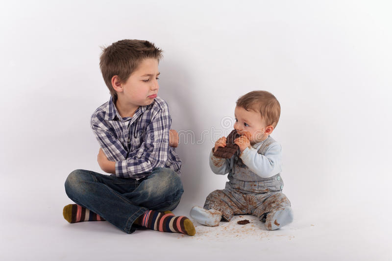 Siblings conflict because of a plate of chocolate royalty free stock images